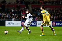 Swansea, UK. Thursday 20 February 2014<br /> Pictured: Leon Britton kicks the ball past Marek Hamsik  of Napoli<br /> Re: UEFA Europa League, Swansea City FC v SSC Napoli at the Liberty Stadium, south Wales, UK