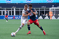 FOXBOROUGH, MA - JULY 25: Djordje Mihailovic #8 of CF Montreal fends off a tackle by Brandon Bye #15 of New England Revolution during a game between CF Montreal and New England Revolution at Gillette Stadium on July 25, 2021 in Foxborough, Massachusetts.