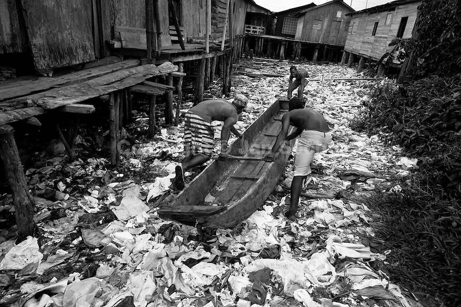Displaced boys push the canoe over the garbage patch in the stilt house area in Tumaco, Nariño dept., Colombia, 18 June 2010. With nearly fifty years of armed conflict, Colombia has the highest number of civil war refugees in the world. During the last ten years of the civil war more than 3 million people have been forced to abandon their lands and to leave their homes due to the violence. Internally displaced people (IDPs) come from remote rural areas, where most of the clashes between leftist guerrillas FARC-ELN, right-wing paramilitary groups and government forces takes place. Displaced persons flee in a hurry, carrying just personal belongings, and thus they inevitably end up in large slums of the big cities, with no hope for the future.