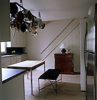 A Swedish-style kitchen has simple white-painted wooden cupboards with granite tops and a white-painted floor
