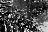 """Switzerland. Canton Uri. Rütli. Twenty competitors and members of the riflemen's association aim their rifles and automatic or semi-automatic assault rifles SG 550 during the Rütlischiessen. Rütli or Grütli is a mountain meadow overlooking the lake Lucerne where the oath of the Rütlischwur for the forming of the Old Swiss Confederacy is said to have occurred as the legendary turning-point in the pursuit of independence. To commemorate this historic event, the riflemen's association of Lucerne organized the Rütli rifle match (Rütlischiessen) in 1862. It is held every year on the Wednesday before Martinmas (Saint Martin's Day). Thousand competitors from all over Switzerland fire their fifteen shots at targets arranged on a cliff. The SG 550 is an assault rifle manufactured by Swiss Arms AG (formerly Schweizerische Industrie Gesellschaft) of Neuhausen, Switzerland. """"SG"""" is an abbreviation for Sturmgewehr, or """"assault rifle"""". The rifle is based on the earlier 5.56mm SG 540 and is also known as the Fass 90 or Stgw 90. An assault rifle is a selective-fire rifle that uses an intermediate cartridge and a detachable magazine. 9.11.2016 © 2016 Didier Ruef"""