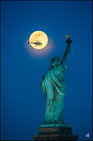 The Statue of Liberty with a full moon and a helicopter.