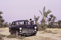 Palmeraie de Marrakech. Un homme avec une voiture devant les palmiers - Marrakech, Maroc - 1973<br /> <br /> on the outskirts of Marrakesh. A Peugeot 404 car with a driver.1973