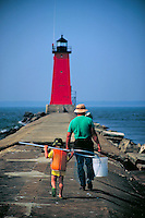 Grandfather and grandson going fishing on the pier of the Lake Michigan lighthouse, lighthouses, generations, family. Manistique Michigan USA.
