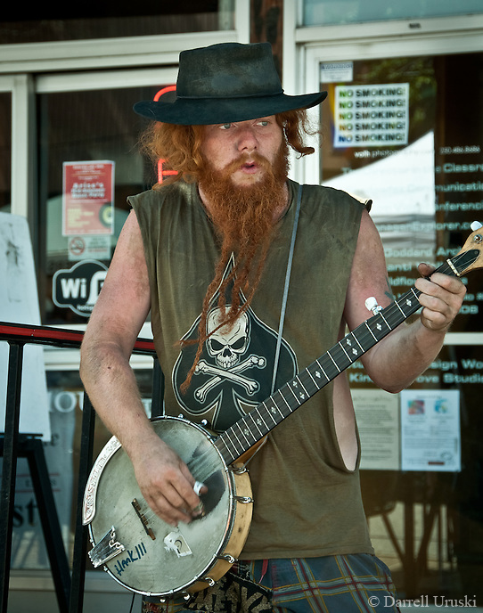 Street photography, of a cool red hair dude playing the banjo on the street.
