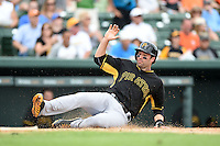 Second baseman Neil Walker (18) of the Pittsburgh Pirates slides into home during a spring training game against the Baltimore Orioles on March 23, 2014 at McKechnie Field in Bradenton, Florida.  Baltimore and Pittsburgh played to a 7-7 tie.  (Mike Janes/Four Seam Images)