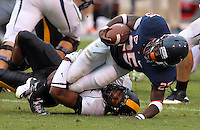 Virginia Cavaliers running back Kevin Parks (25) is tackled by a Southern Miss Golden Eagles defender during the game at Scott Stadium. Virginia was defeated 30-24. (Photo/Andrew Shurtleff)