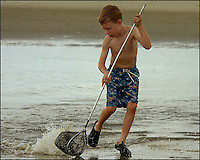 A young boy (model released) plays on the ocean beach on a summer day. Photo taken on Sullivan's Island, near Charleston, South Carolina beach on the Atlantic Ocean, but could represent a beach scene anywhere.