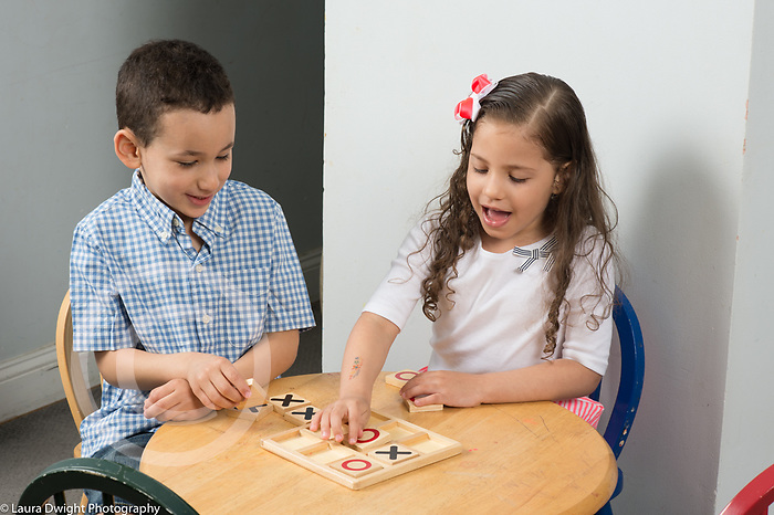 4 year old boy and 5 year old friend playing tic tac toe game using wooden toy pieces