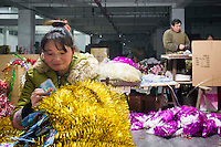 November 28, 2015, Yiwu, China - A female migrant worker makes bundles of tinesel by hand at the Xin Shua tinsel factory. She is paid 0.04 RMB for each bunch of tinsel she tags together by hand and her tally is added to that of her mother. The factory makes around 30 million RMB (GPB 3.12) of tinsel each year.Photo by Dave Tacon / Sinopix