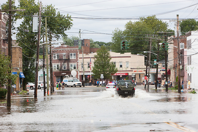 MAMARONECK, NY - AUGUST 28: A village police cruiser leads a vehicle through flood waters on Mamaroneck Avenue, as local residents look on, in the Village of Mamaroneck, New York on Sunday August 28, 2011 in the aftermath of Hurricane Irene.