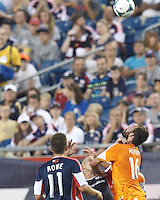 New England Revolution forward Chad Barrett (9) and Houston Dynamo midfielder Adam Moffat (16) battle for head ball.  In a Major League Soccer (MLS) match, Houston Dynamo (orange) defeated the New England Revolution (blue), 2-1, at Gillette Stadium on July 13, 2013.