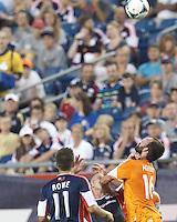 New England Revolution forward Chad Barrett (9) and Houston Dynamo midfielder Adam Moffat (16) battle for head ball.  In a Major League Soccer (MLS) match, Houston Dynamo (orange) defeated the New England Revolution (blue), 2-1, at Gillette Stadium on July 13, 2013.
