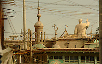 The crested moon from a mosque is juxtaposed against a statue of Chairman Mao in the old town of Kashgar, Xinjiang Province, China. Kashgar is within a few hundred kilometers of the Afghanistan, Pakisthan and Indian borders and it's people mostly belong to the 20 million ethnic Uihgurs, who do not consider themselves Chinese but part of lost state of Turkestan. The Uihgurs have been fighting an underground gorilla war and certain groups are seen as terrorists by the Communist Party..