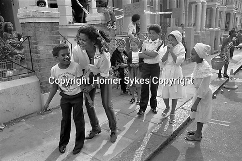 Notting Hill London 1980s UK An older woman with young kid being friendly, other children and adults watching having fun, laughing in the street. During the annual Notting Hill Carnival. 1980s England