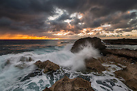 A wave explodes off the rocky shoreline of Pupukea Marine Reserve while the sun sets, North Shore, O'ahu.