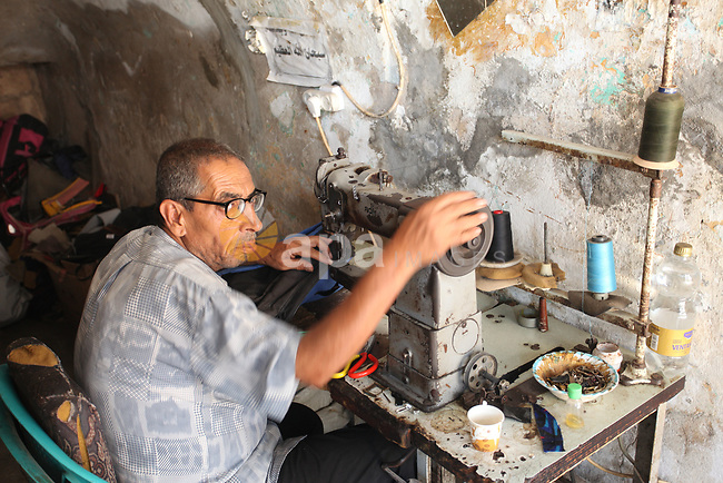 Palestinian tailor Khalil Hamdan, 64, re-sewing worn out shoes and bags for students before the start of the new school year, in light of difficult economic and living conditions for Gazans, at al-Zawya market in Gaza city on August 10, 2021. The fiscal position in Gaza strip has worsened not only due to the outbreak but also due to a political standoff that is disrupting the flow of revenues. The outlook remains precarious and subject to numerous political, security and health risks. Photo by Youssef Abu Watfa