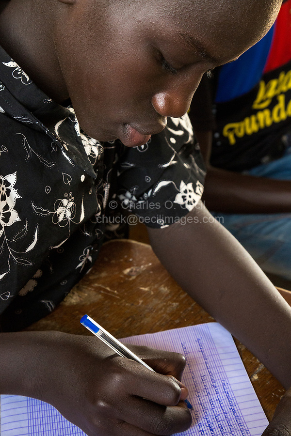 Senegal, Touba.  Young Man at Al-Azhar Madrasa, a School for Islamic Studies, Writing in Arabic in his Notebook.