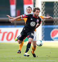 Brad Davis (11) of the Houston Dynamo tries to stop the run of Nick DeLeon (18) of D.C. United during a Major League Soccer game at RFK Stadium in Washington, DC. D.C. United vs. Houston Dynamo, 2-1.