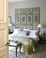 A pair of 18th century-style painted panels decorates the wall above the bed in the master bedroom