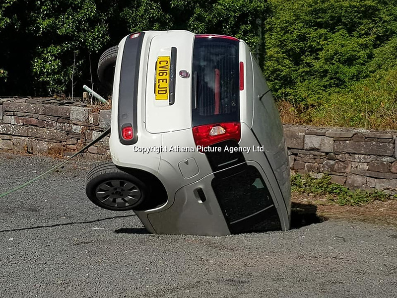 """Pictured: The white Fiat Panda car which ended up inside a sinkhole in the car park of Craig Y Nos castle in Wales, UK. Saturday 18 August 2018<br /> Re: A car has fallen into a sinkhole in the car park of Craig Y Nos castle in the Brecon Beacons, Wales, UK.<br /> Luke Davies was surprised when he got a call from his father asking him to go up to the castle where his mother was working.<br /> He went under the impression that it was not that serious.<br /> The hole was about 18-20 feet at its deepest, and the car had fallen in bonnet-first and was wedged against the other side of the hole.<br /> """"It must have happened within five to 10 minutes, Mr Davies, 30, from Coelbren in Powys, said.<br /> A visitor had seen it happen and alerted staff, who told his mother, Karen.<br /> The general manager managed to attach a tow rope to the car to prevent it from falling further.<br /> It is thought that the sinkhole has been caused by an underground stream of water, possibly leading to erosion under the overflow car park.<br /> Once the recovery vehicle arrived, they considered using a crane as they were concerned about further damaging the car.<br /> The door panels were damaged and one of the rear doors couldn't be opened."""