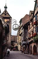 Riquewihr: Main Street to gate. Brick street, half-timbered buildings.