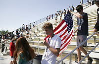 Eric Pedersen (from left) and Carson Shipman carry a flag as they walk steps, Thursday, September 9, 2021 at Tiger Stadium in Bentonville. The district is educating students on the 9/11 attacks. Students completed 40 climbs up the home bleachers, the equivalent of the 110 stories (2200 stairs) of the Twin Towers. Check out nwaonline.com/210910Daily/ for today's photo gallery. <br /> (NWA Democrat-Gazette/Charlie Kaijo)