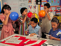 HISPANIC ELEMENTARY SCHOOL CHILDREN MAKE A PiNATA IN CLASS FOR FIESTA PARTY. ELEMENTARY SCHOOL CHILDREN. SAN ANTONIO TEXAS.