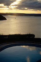 The sun sets over the Indian Ocean and the swimming pool at a lodge in Kilifi
