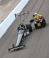 Feb 22, 2014; Chandler, AZ, USA; NHRA top fuel dragster driver Terry McMillen is pushed off the track by a member of the Safety Safari during qualifying for the Carquest Auto Parts Nationals at Wild Horse Motorsports Park. Mandatory Credit: Mark J. Rebilas-USA TODAY Sports