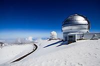 Telescopes on top of Mauna Kea Mountain, under the snow, with a beautiful blue sky, on the Hawaii Big Island