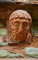 Norman Romanesque exterior corbel no 89 - sculpture of a male with curly hair and theatrical style mouth. The Norman Romanesque Church of St Mary and St David, Kilpeck Herefordshire, England. Built around 1140