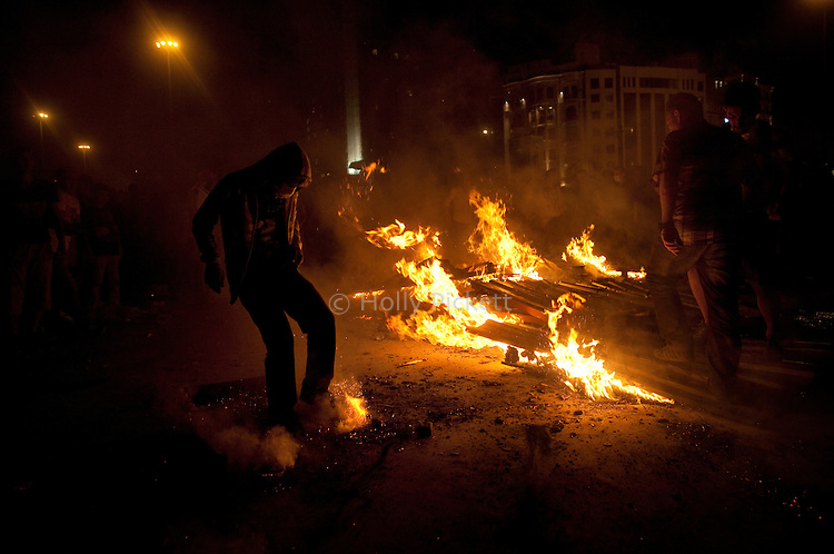 Protesters try to put out a fire in Taksim Square, Istanbul, Turkey, June 1, 2013. What started as a peaceful sit-in to save a small park near Taksim Square from being turned into a shopping mall has turned into large-scale anti-government demonstrations in cities across Turkey.