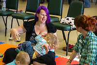 """Breastfeeding a toddler at a singing and signing group whilst talking to the other mothers.Image from the breastfeeding collection of the """"We Do It In Public"""" documentary photography picture library project: <br />  www.breastfeedinginpublic.co.uk<br /> <br /> <br /> Berkshire, England, UK<br /> 27/09/2013<br /> <br /> © Paul Carter / wdiip.co.uk"""