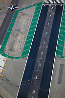 aerial photograph of a small jet holding in position for its takeoff as a Continental airliner taxis for takeoff at Lindberg Field, San Diego International Airport (SAN), San Diego, California