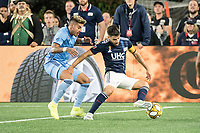 FOXBOROUGH, MA - SEPTEMBER 29: Ronald Matarrita #22 of New York City FC comes in to tackle Carles Gil #22 of New England Revolution during a game between New York City FC and New England Revolution at Gillettes Stadium on September 29, 2019 in Foxborough, Massachusetts.