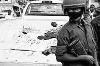 Man arrested in back of pick up truck being guarded by masked Haitian police outside a voting station on Delmas.