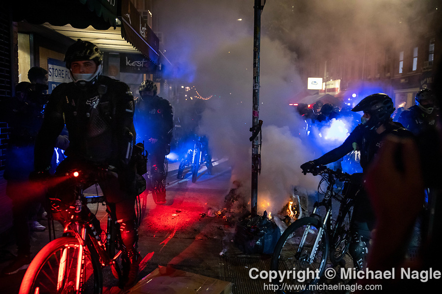 NYPD police officers pass by a fire during a protest demanding every vote cast be counted in the 2020 presidential election between U.S. President Donald Trump and former Vice President Joe Biden on November 4, 2020 in New York City.  Photograph by Michael Nagle
