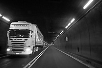 Switzerland. Canton Ticino. Gotthard Road Tunne. A truck delivering merchandise rides the tunnel. The Gotthard Road Tunnel runs from Göschenen in the canton of Uri at its northern portal, to Airolo in Ticino to the south, and is 16.9 kilometres in length below the St Gotthard Pass, a major pass of the Alps. Although it is a motorway tunnel, part of the A2, it consists of only one bidirectional tube with two lanes. 1.12.2020 © 2020 Didier Ruef
