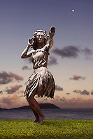 Hula dancer sculpture at sunset with ocean scenery.