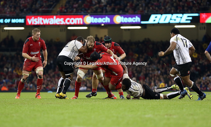 Pictured: Alun Wyn Jones of Wales (C) is brought down by Sunia Koto of Fiji. Saturday 15 November 2014<br /> Re: Dove Men Series rugby, Wales v Fiji at the Millennium Stadium, Cardiff, south Wales, UK.