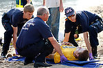 EMTs carrying a victim on a backboard after being hurt on a beach