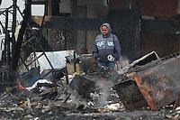 FOTO EMBARGADA PARA VEICULOS INTERNACIONAIS. SAO PAULO, SP, 15-11-2012, RESCALDO FAVELA PENHA. Moradores da favela que pegou fogo ontem na Rua Guaiauna no bairro da Penha, tentam recuperar objetos pessoais e documentos no meio das cinzas. Bombeiros ainda continuam no local pois ainda existe caloria em meio aos escombors. Luiz Guarnieri/ Brazil Photo Press