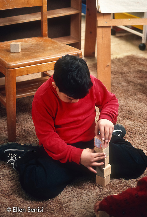 """MR / Schenectady, NY. Yates Arts in Education Magnet Elementary School. Special education classroom. Boy (9, Puerto Rican-American, Down Syndrome) exhibiting incorrect """"W"""" sitting on floor playing with blocks. MR: Abr1. © Ellen B. Senisi"""