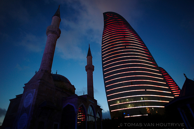 Imam Huseyn Mosque is seen next to the Flame Towers in Baku, Azerbaijan at dusk.