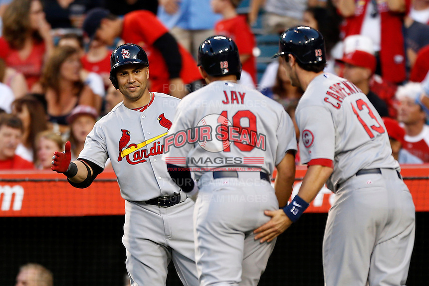 Carlos Beltran #3 of the St. Louis Cardinals welcomes teammates Jon Jay #19 and Matt Carpenter #13 during a game against the Los Angeles Angels at Angel Stadium on July 3, 2013 in Anaheim, California. (Larry Goren/Four Seam Images)