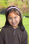 Vietnamese American second grade female smiles with sun on her face in head and shoulders portrait in New Orleans