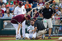Mississippi State first baseman Wes Rea (35) talks with  head coach John Cohen (11) and the training staff while sitting on the ground after a collision during Game 1 of the 2013 Men's College World Series Finals against the UCLA Bruins on June 24, 2013 at TD Ameritrade Park in Omaha, Nebraska. The Bruins defeated the Bulldogs 3-1, taking a 1-0 lead in the best of 3 series. (Andrew Woolley/Four Seam Images)