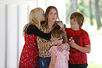 Erica Kelso, receives a kiss from her daughter Maggie, 14, as she is hugged by her daughter Sophie, 7, and son Louie, 10, Friday, April 30, 2021, as she speaks in the carport during a celebration for the completion of her Realtor Build Habitat for Humanity of Washington County home in Fayetteville. Kelso put in more than 300 hours of sweat equity and will pay a monthly affordable mortgage. This is the 57 Habitat for Humanity of Washington County house built in the county since 1991. Check out nwaonline.com/210501Daily/ and nwadg.com/photos for a photo gallery.<br /> (NWA Democrat-Gazette/David Gottschalk)