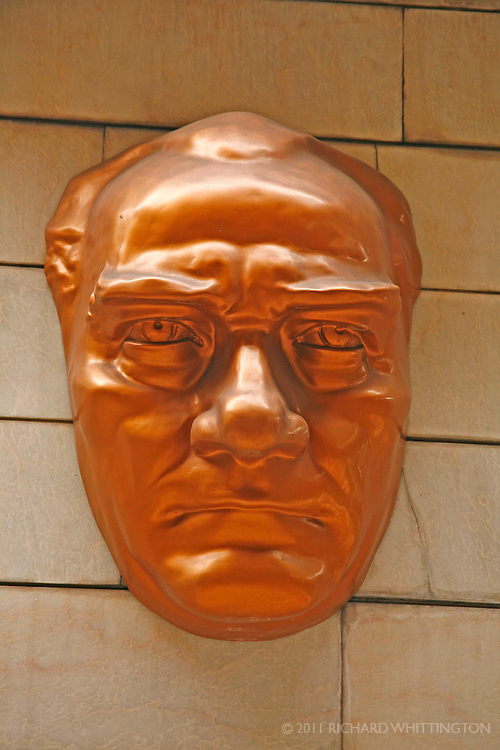 A mask of Mustafa Kemal, more commonly known as Ataturk, hangs on a stone wall. Ataturk was Turkey's first president is known for his modernization and reformation of Turkey. Ataturk's status is legendary, and because of this statues and masks such as this can be found in village squares all around Turkey.